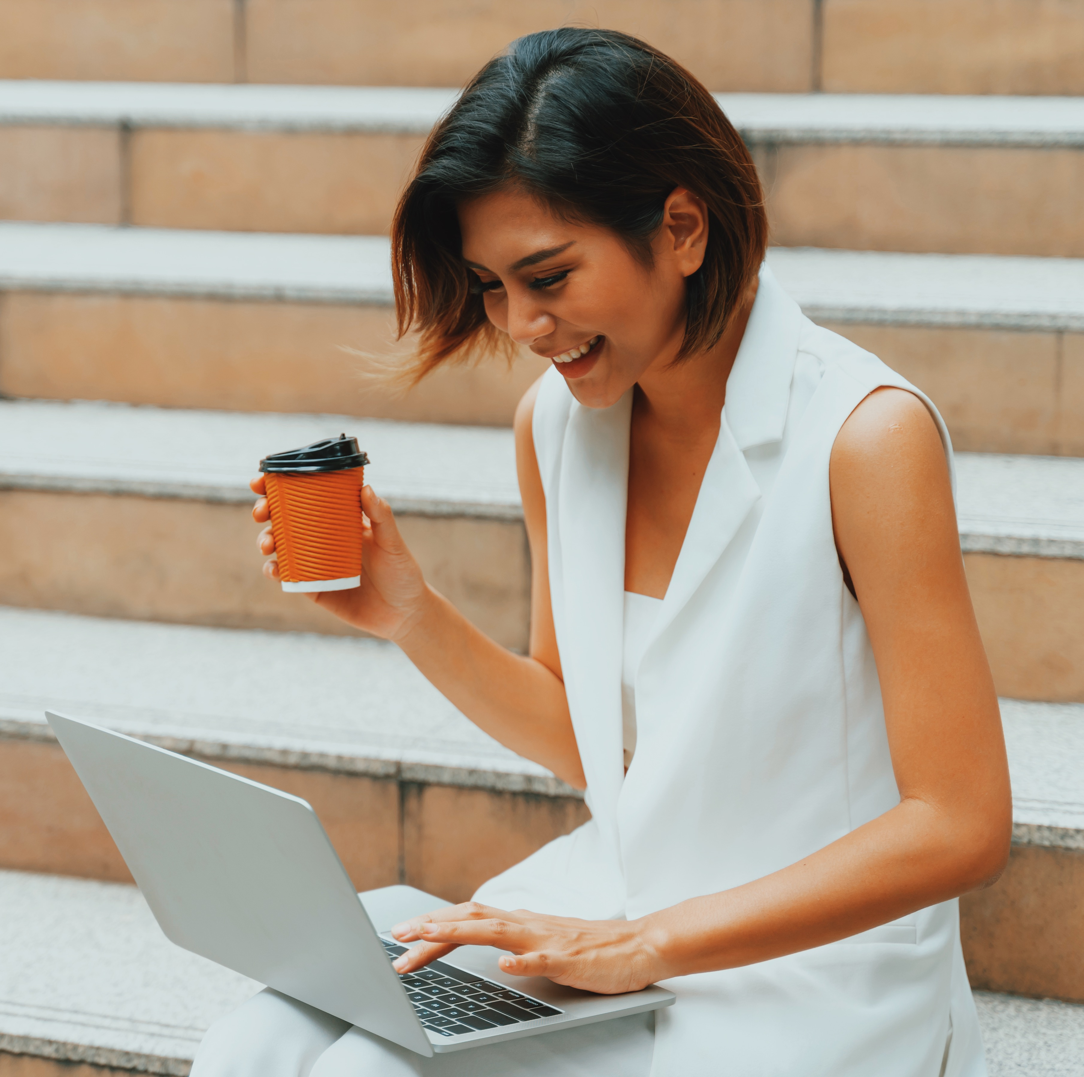 Lady in white vest holding a coffee cup