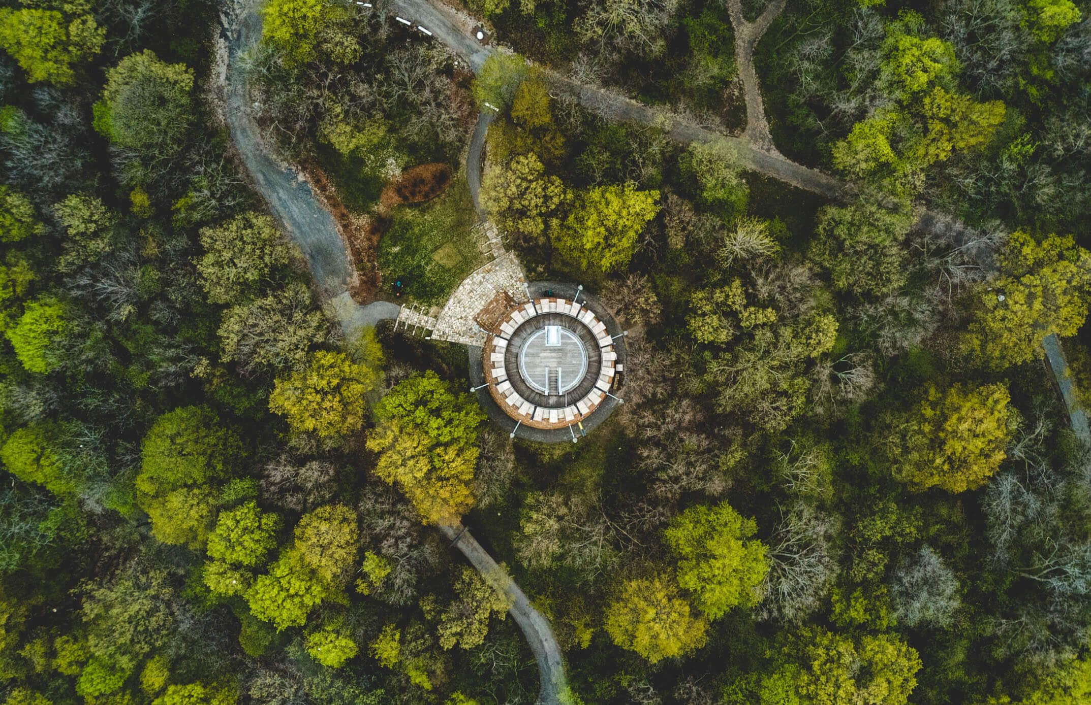 Arial shot of a greenhouse in the middle of a densely wooded, green area