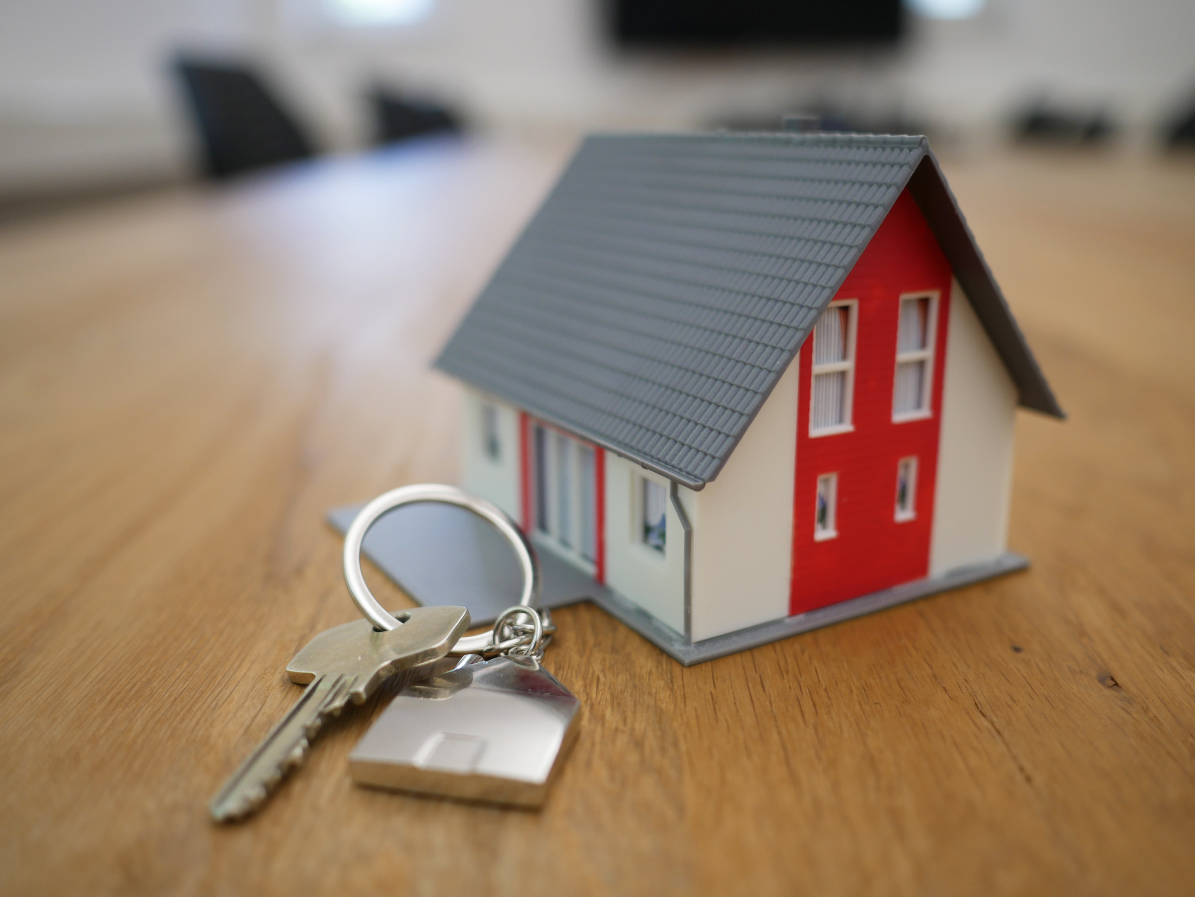 Miniature home with keys sitting on a table.