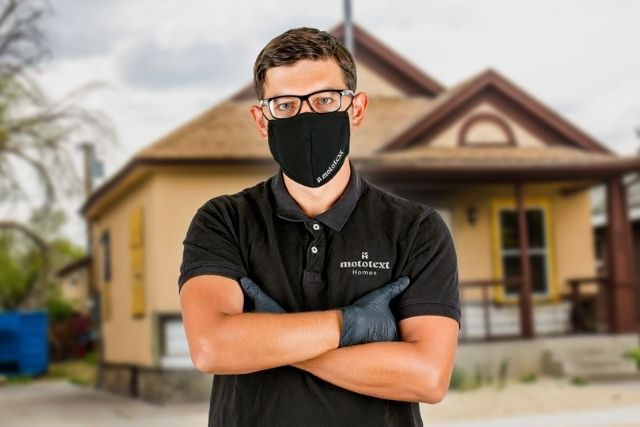 A man standing in front of a home in a mask and gloves.