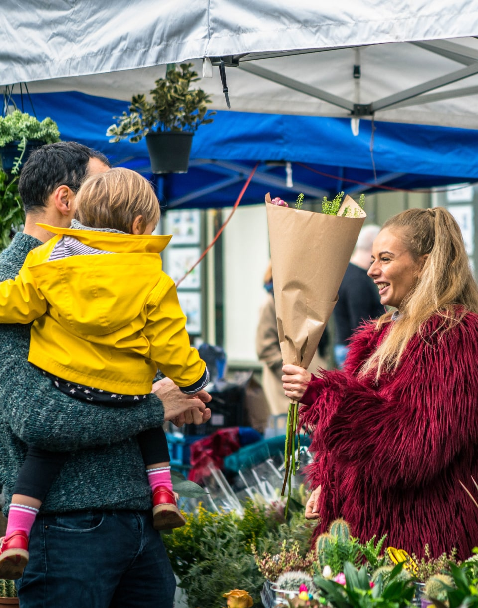 Woman selling flowers at Columbia Road flower market
