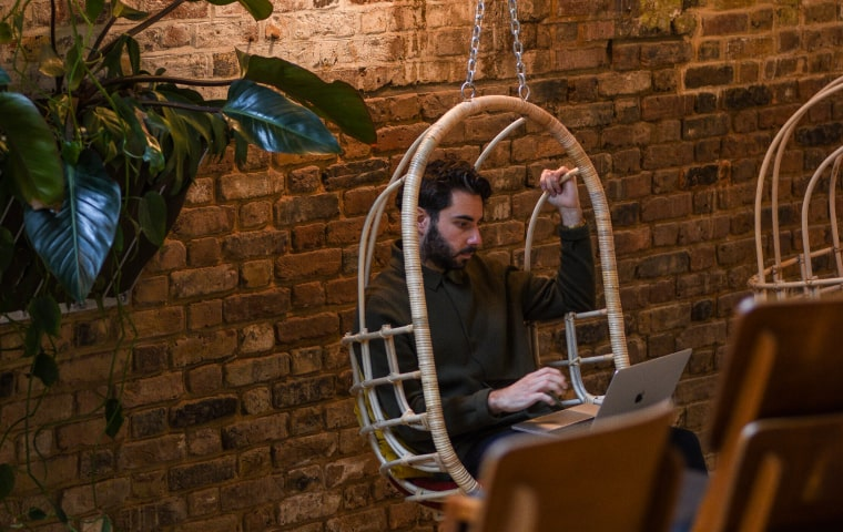 man working on laptop in swinging chair
