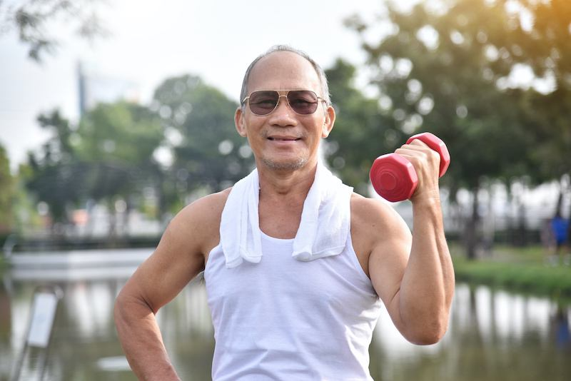 senior male in singled holding a dumbbell weight