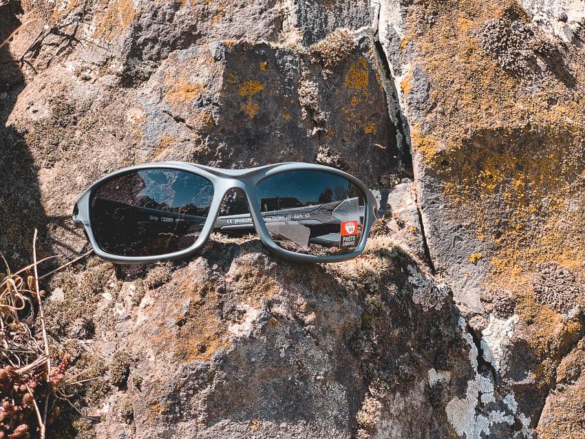 Das Sportbrillen-Modell Grip der Marke Swisseye hängt in einem Fahrradhelm: Peppler Augenoptik Favorit in Puncto Preis-Leistungs-Verhältnis, Funktion und Aussehen.