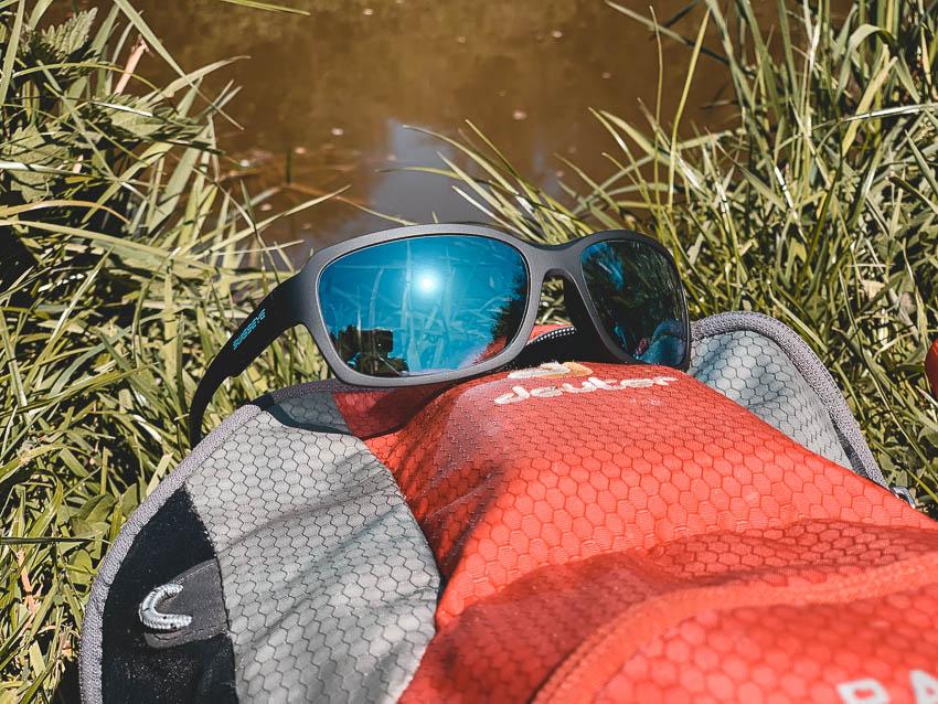 Das Sportbrillen-Modell Ambient der Marke Swisseye hängt in einem Fahrradhelm: Peppler Augenoptik Favorit in Puncto Preis-Leistungs-Verhältnis, Funktion und Aussehen.