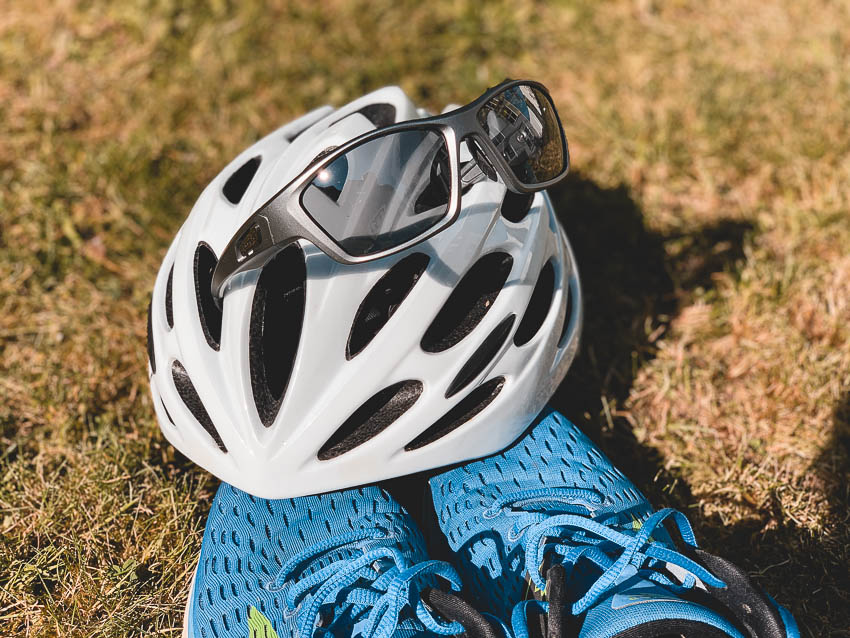 Das Sportbrillen-Modell Trail der Marke Swisseye hängt in einem Fahrradhelm: Peppler Augenoptik Favorit in Puncto Preis-Leistungs-Verhältnis, Funktion und Aussehen.