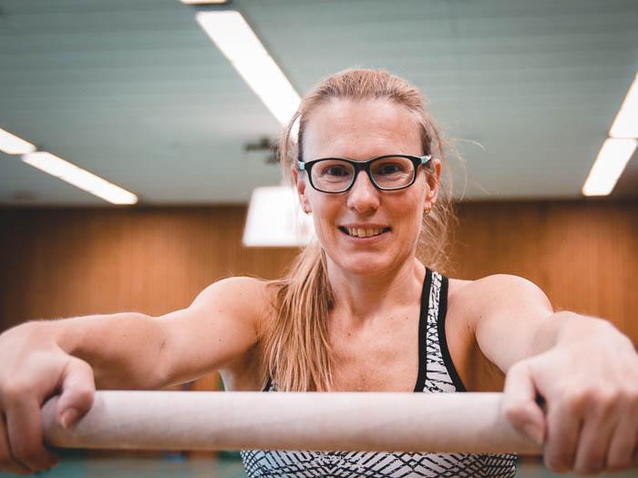 Die Turnerin Katja Leib steht am Barren. Sie trägt eine Indoor-Sportbrille mit ungetönten Gläsern.