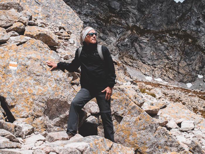Dieter Müller-Peppler steht an einen Felsen. Er trägt eine Sportbrille der Marke Julbo.