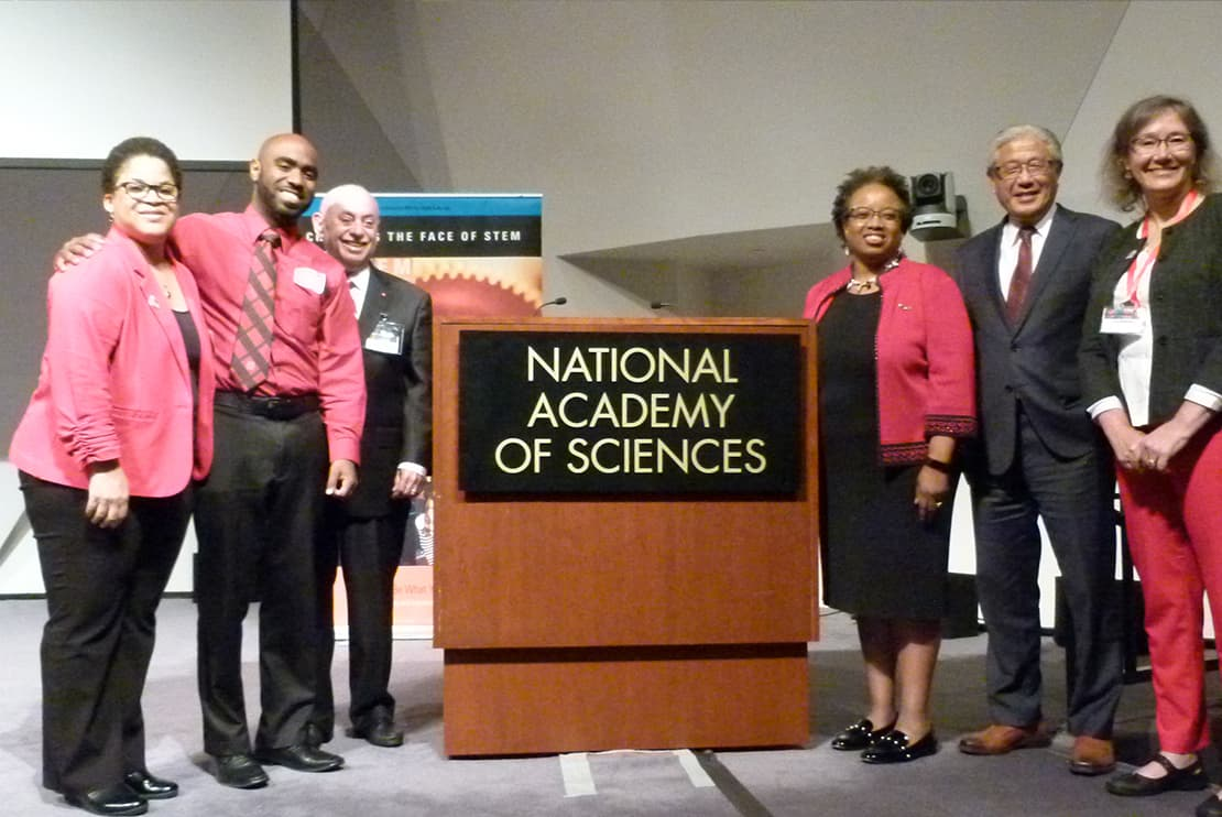 photograph of a group of six people with a range of skin tones smiling surrounding a podium that reads national academy of sciences