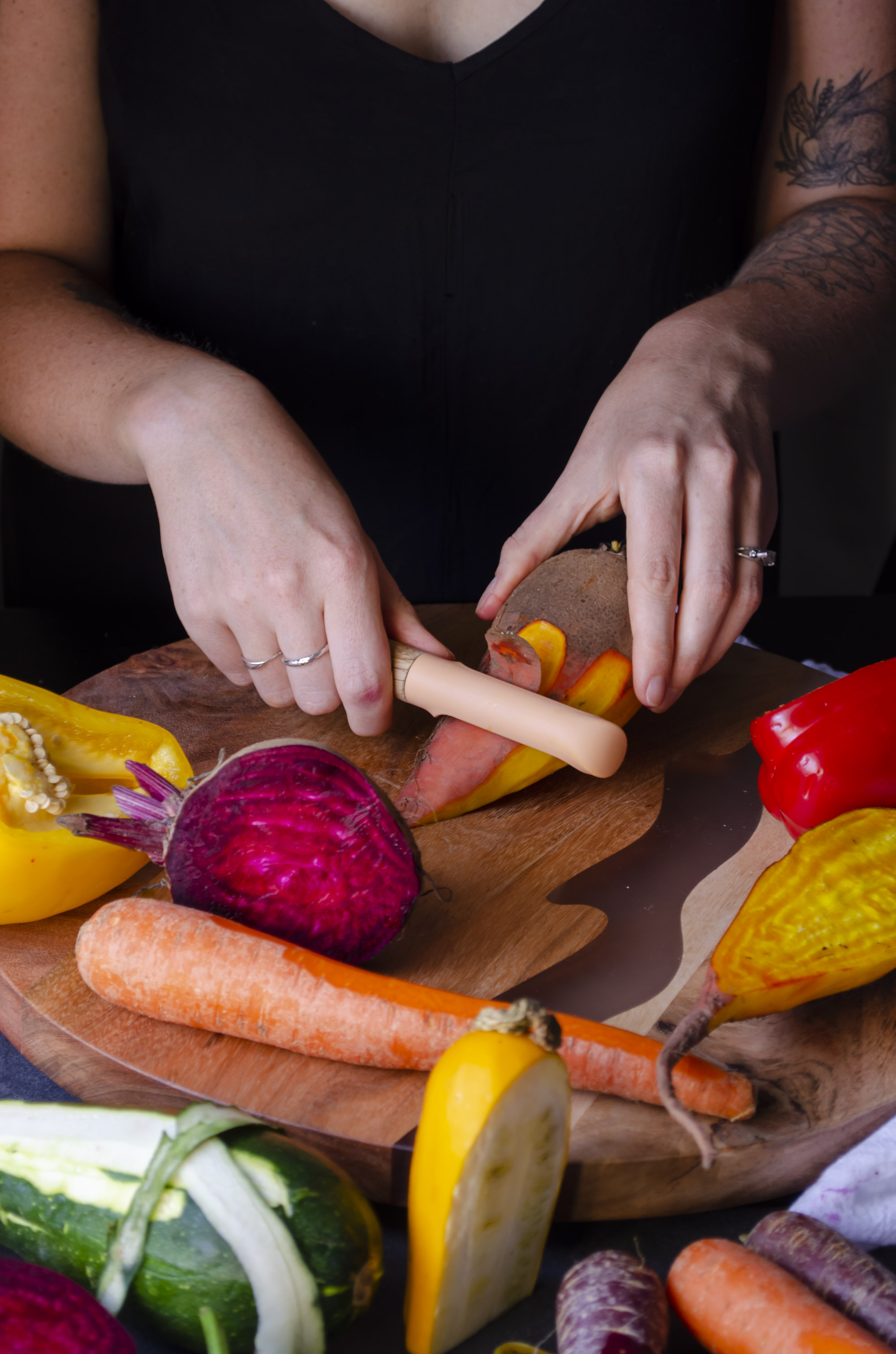 Hands peeling carrots and other vegetables.