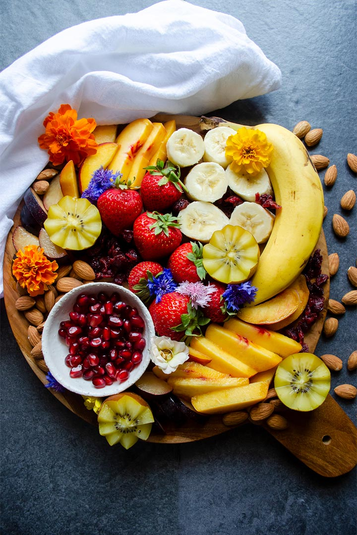 A wooden serving board full of cut fruit on a slate background.