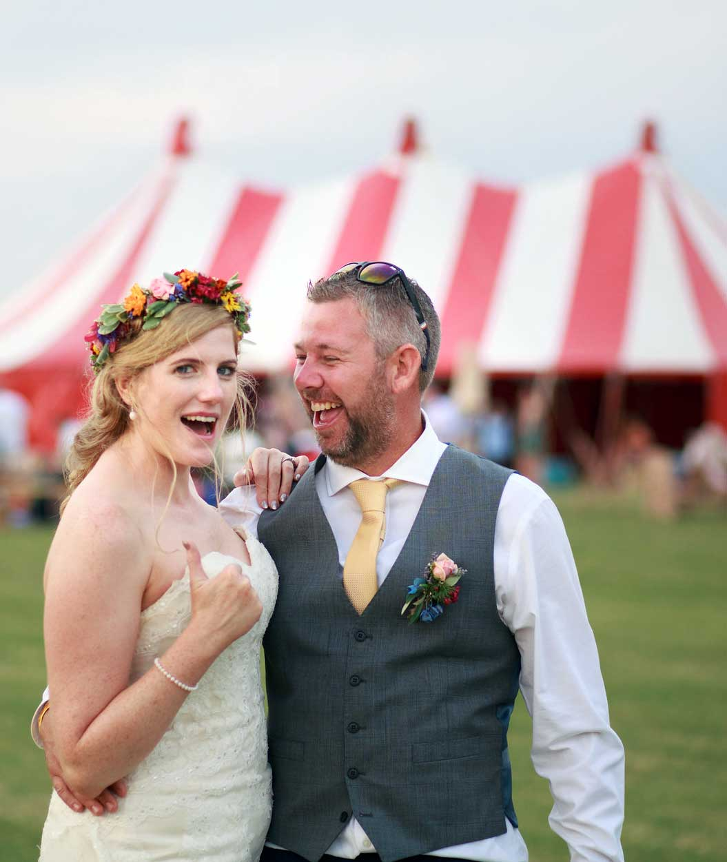 A wedding couple in front of a circus tent