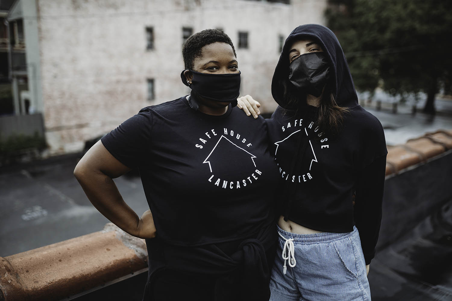 Two women embracing in SafeHouse branded tops