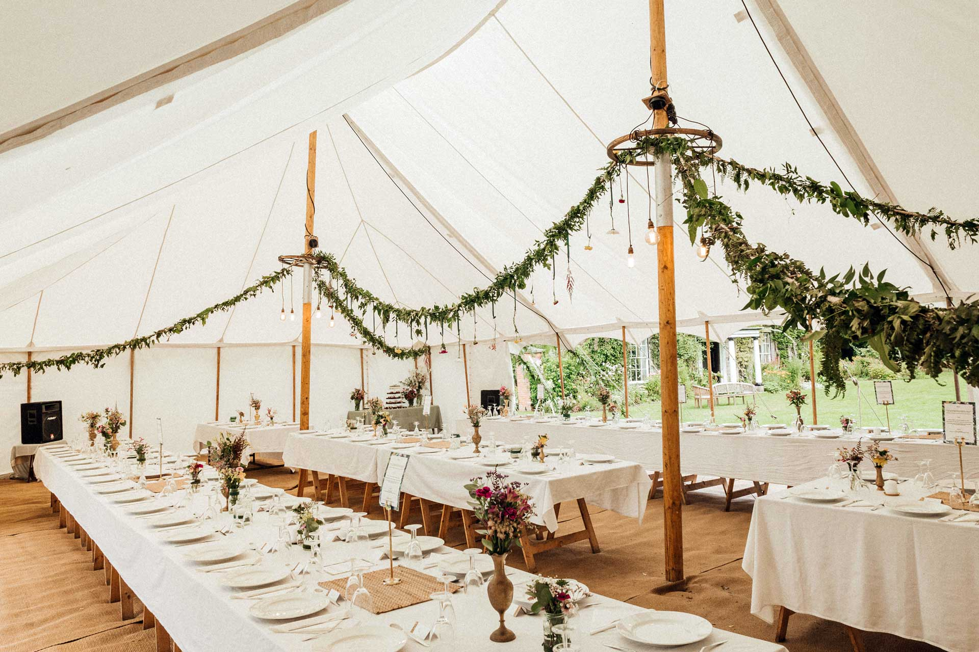 Petal marquee wedding tent with interior bohemian styling and flower garlands