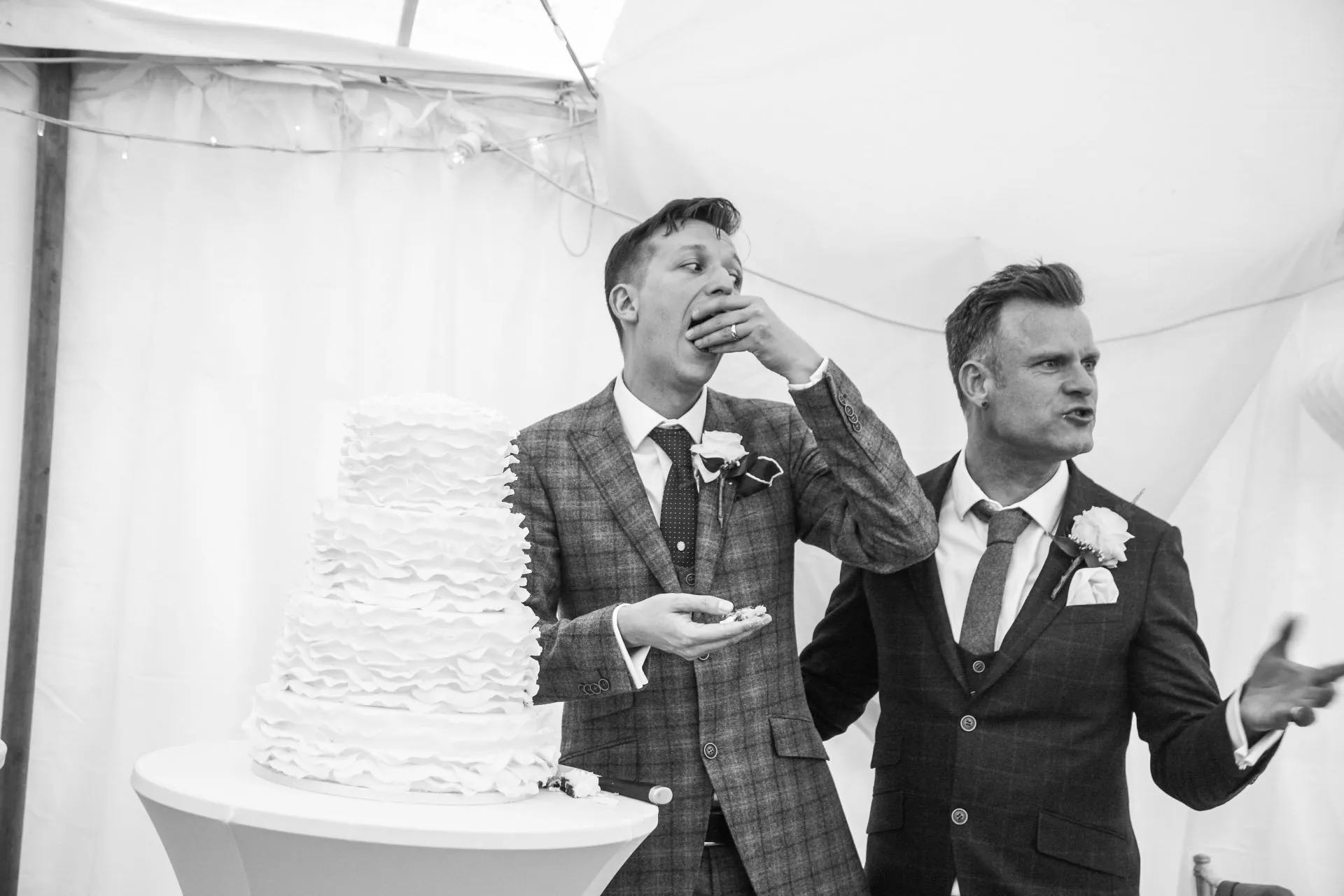 2 grooms enjoy the wedding cake at LGBT wedding ceremony