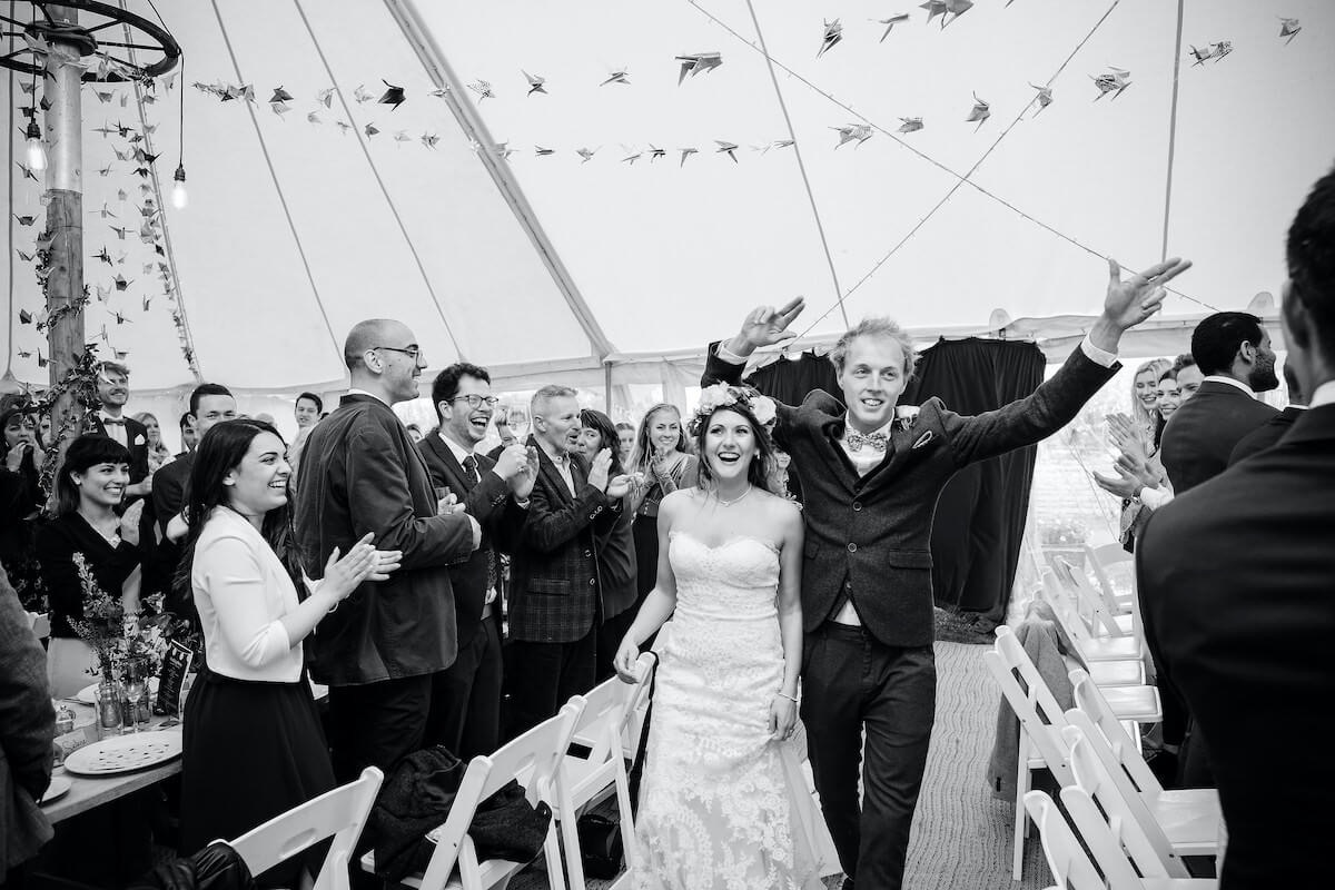 Bride and groom grand entrance into their wedding marquee