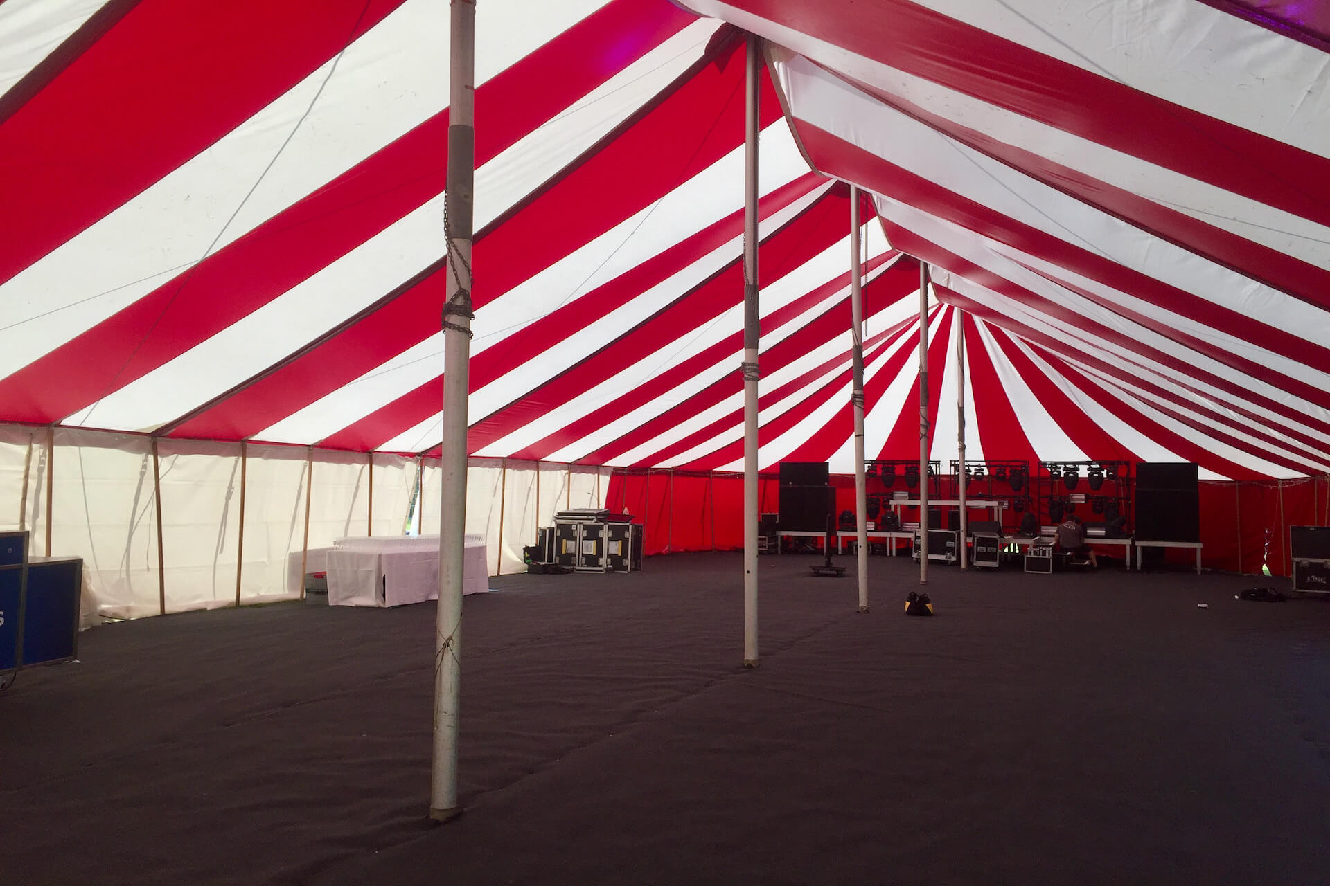 Inside a large red white circus Big Top marquee