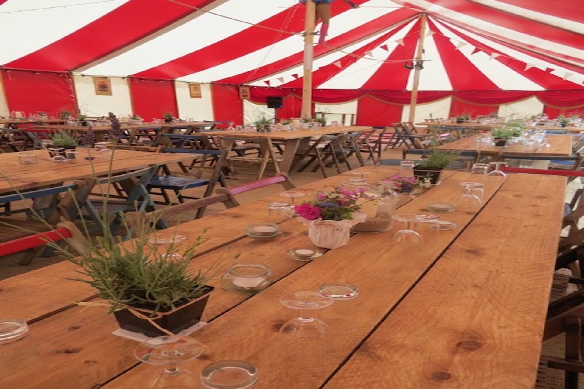 Rustic tables in dinner party marquee