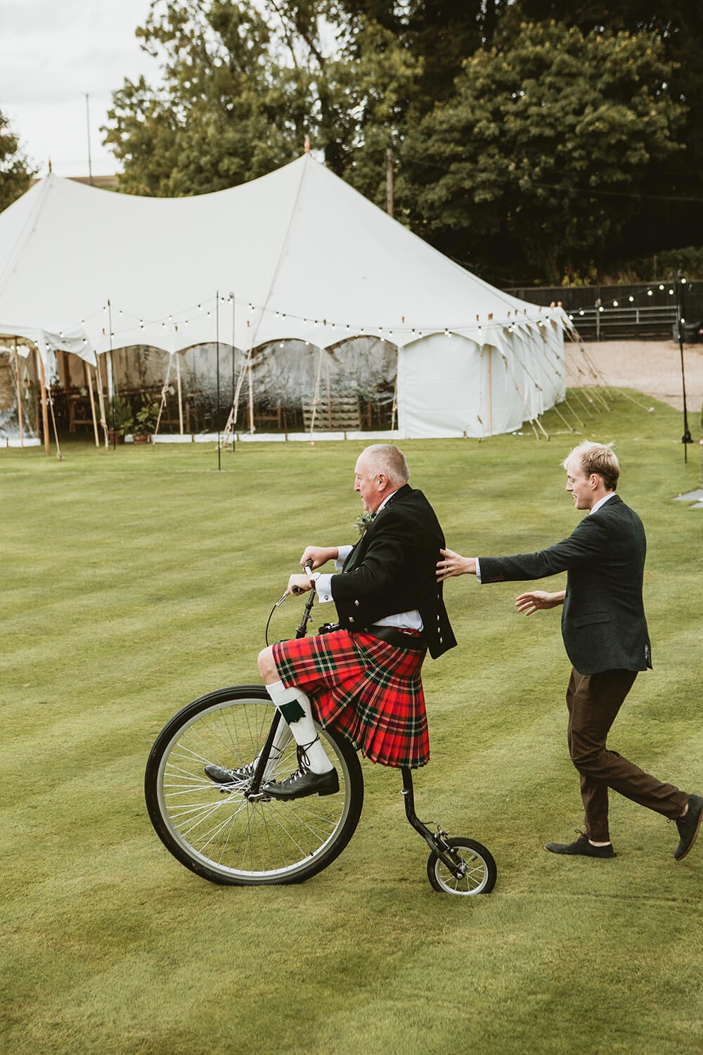 Father of bride riding penny farthing at riverside wedding