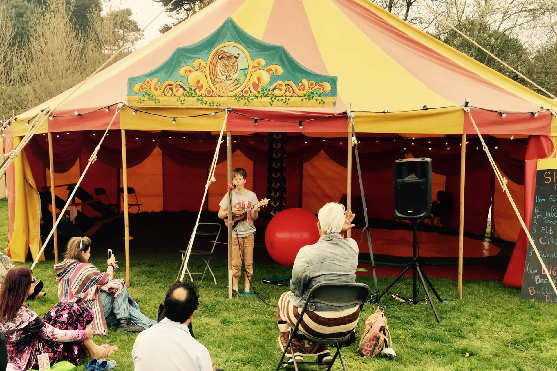 A young singer performs in front of circus tent