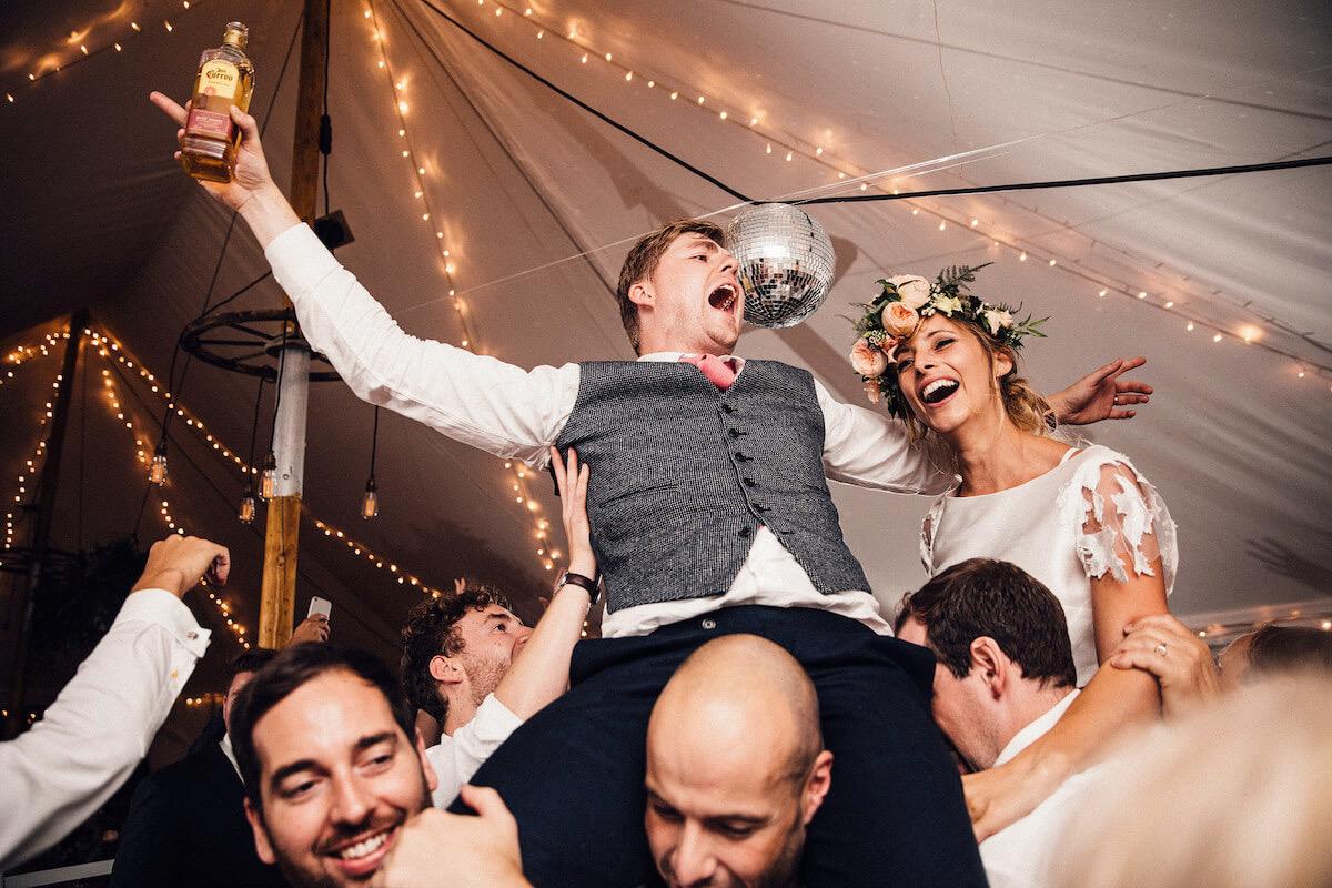 bride Groom on shoulders in a fairy lit marquee