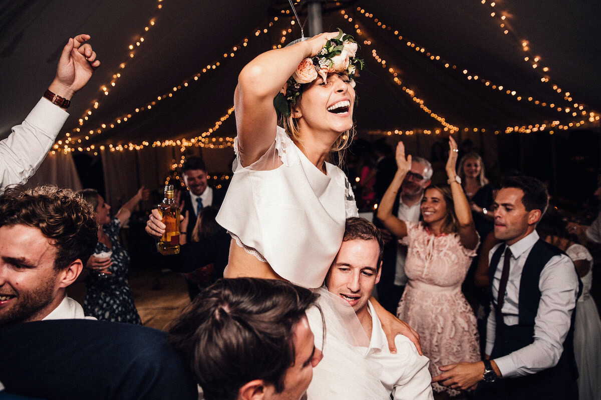 Fairy lights in wedding marquee and bride on shoulders of groom