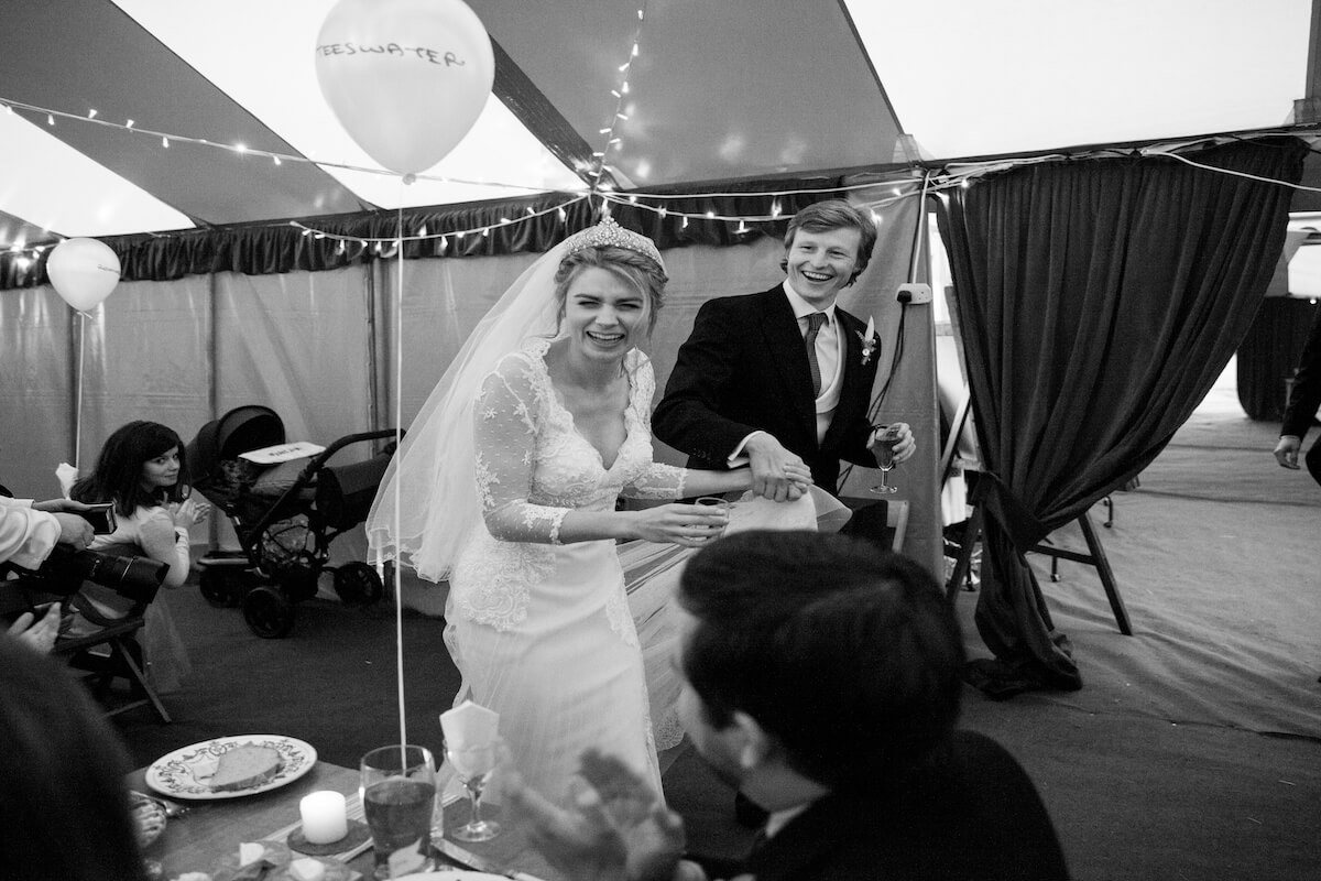 A very happy couple on their wedding day in a big-top