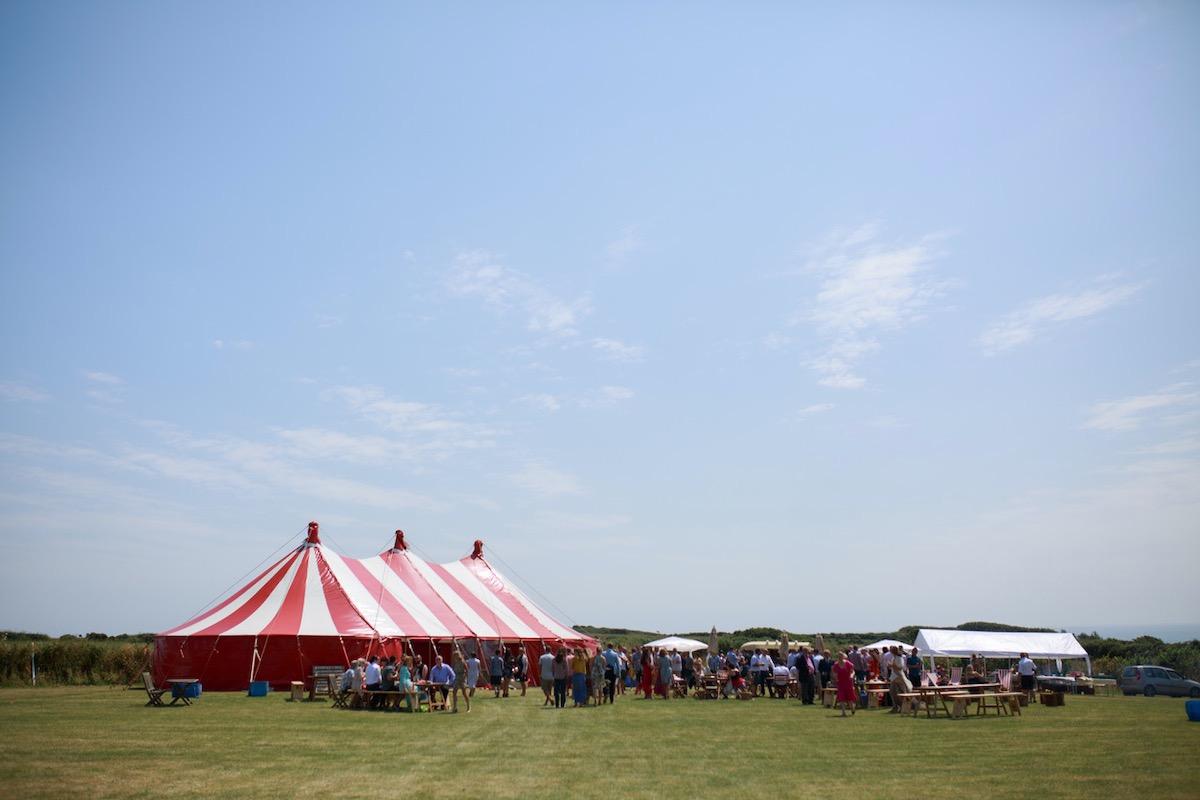 Sunny coastal wedding with a circus style big-top