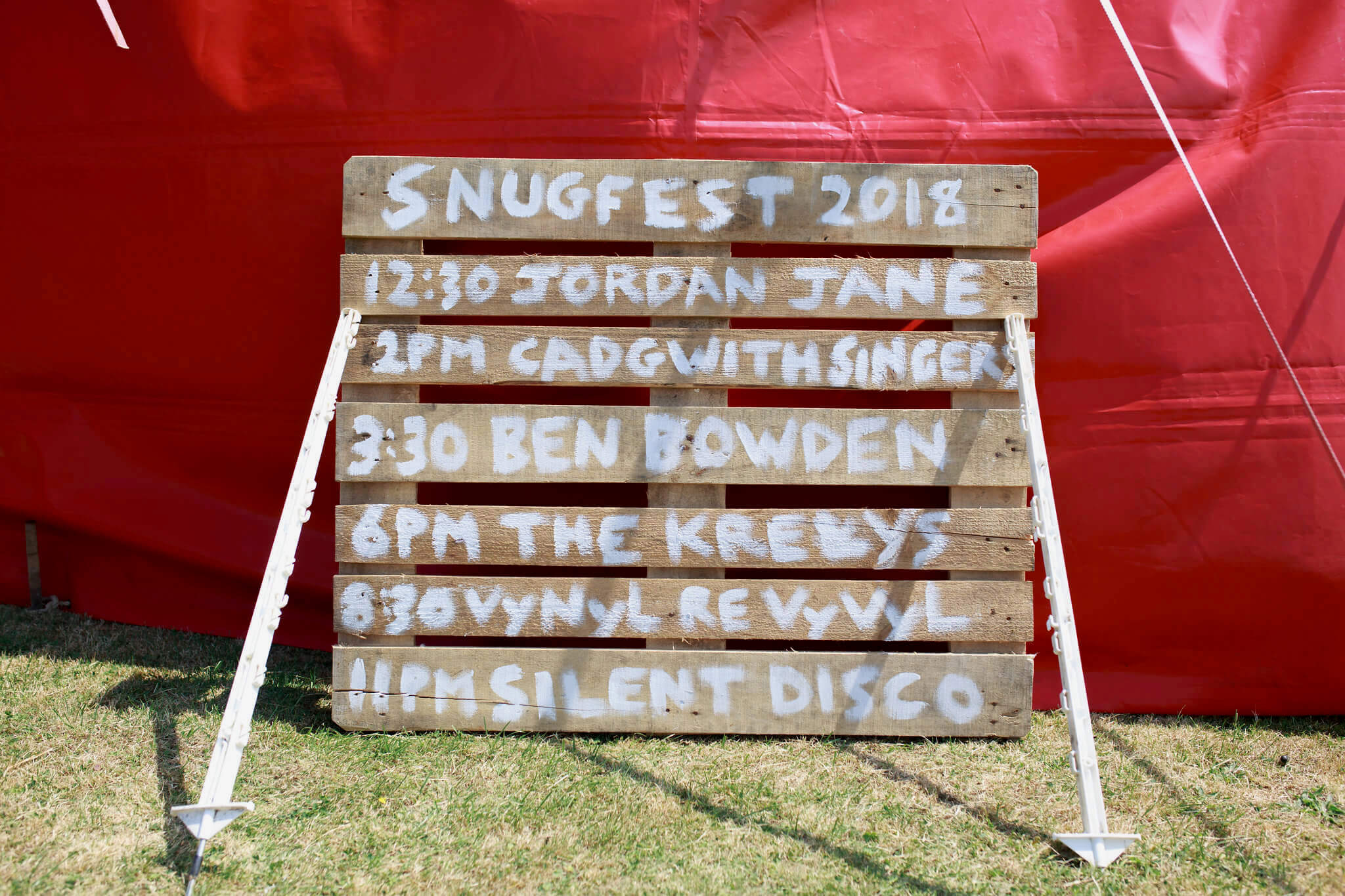 DIY sign with music line up at wedding festival