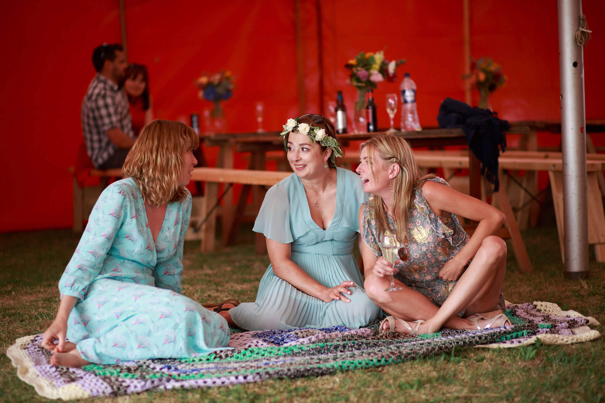 Guests relaxing on blanket at a big-top wedding