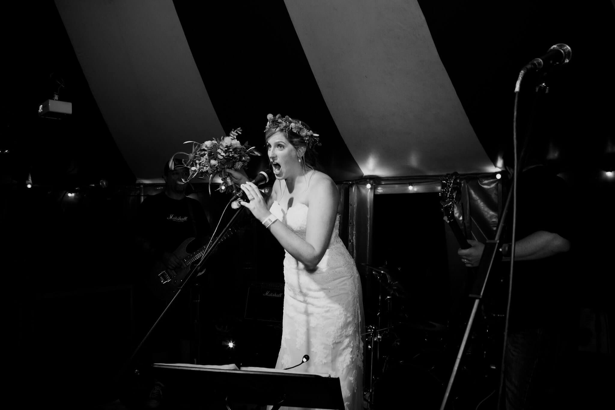 A bride takes to the microphone on stage at her wedding feast