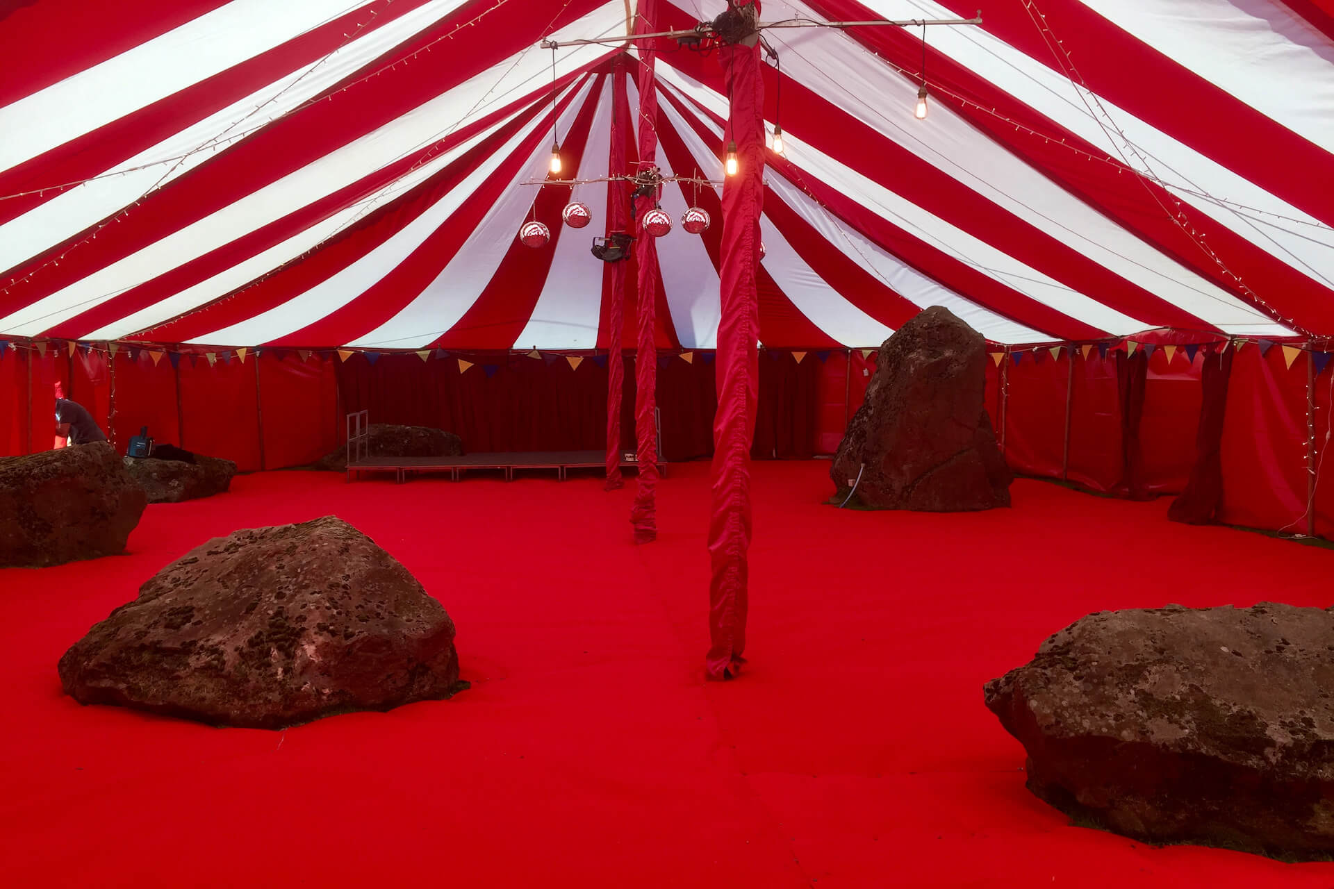 Marquee with red carpet installed over boulders
