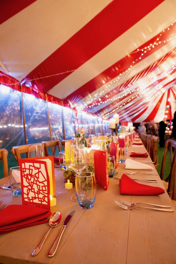 Long trestle tables in colourful marquee