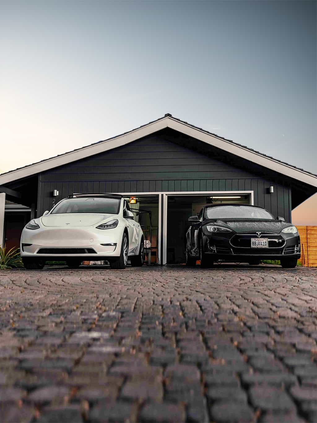 Two Tesla EVs in front of a house.