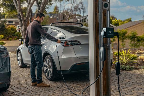 Man charging his electric car at home