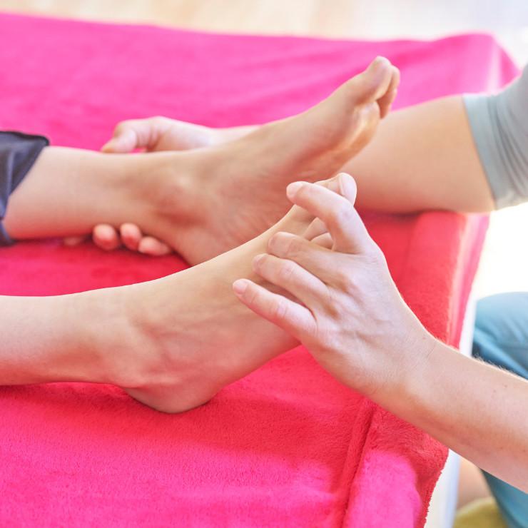 Hände drücken Energiepunkte am Fuß