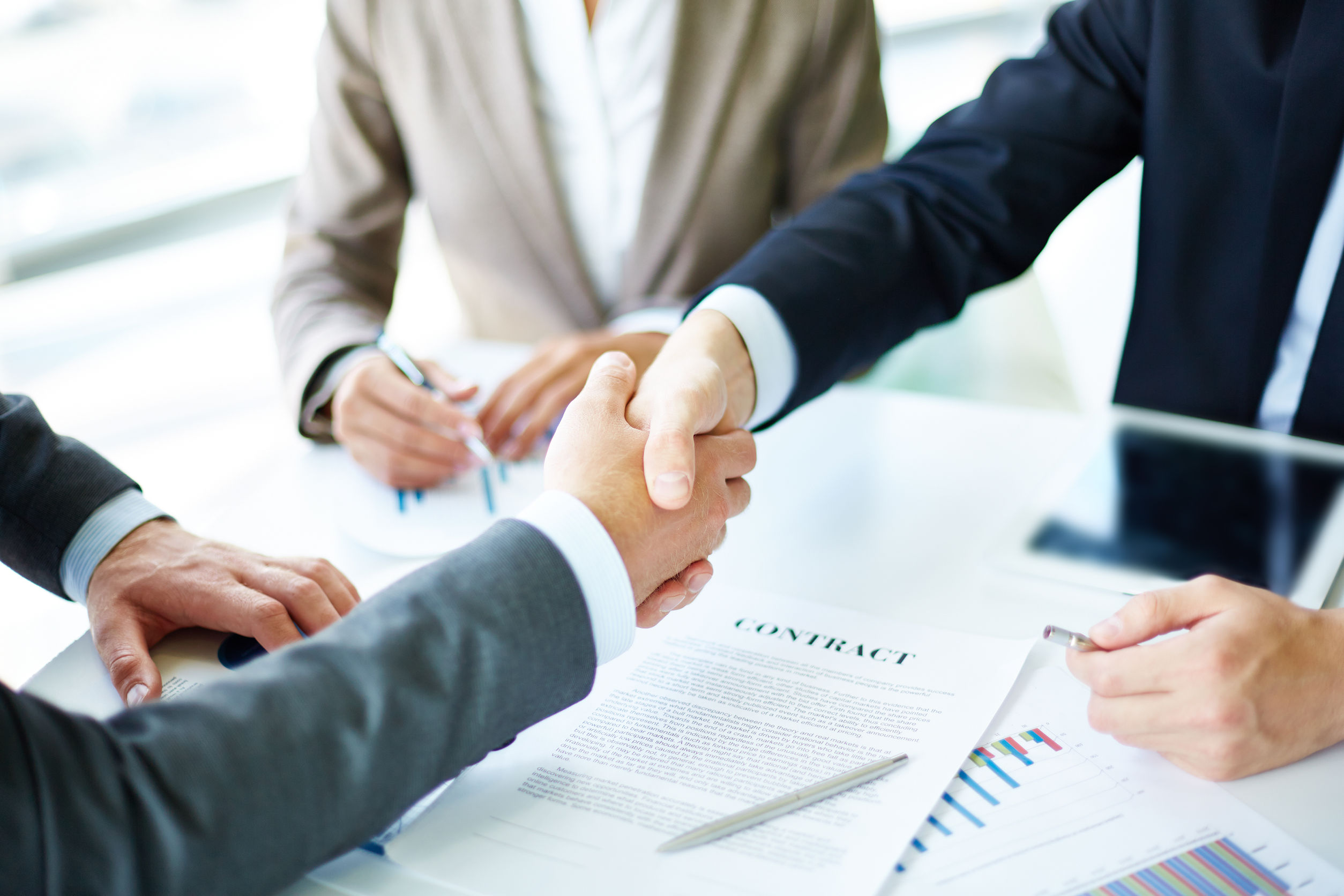 An image of shaking hands over a contract.