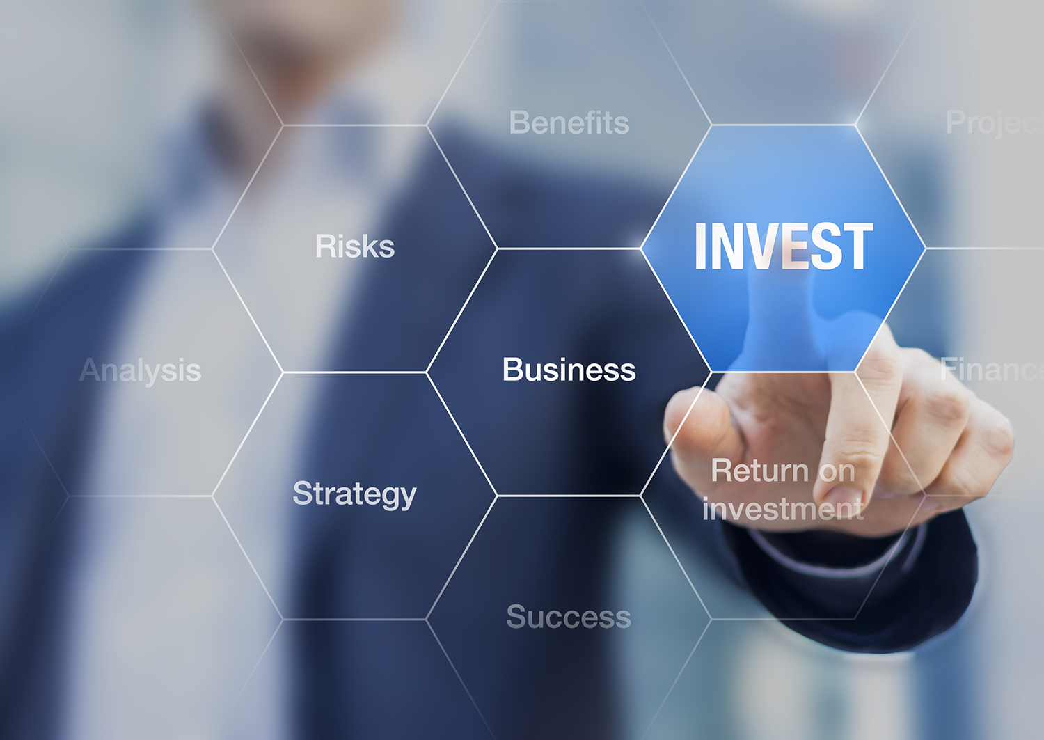 An image of a hand pointing at the word invest.