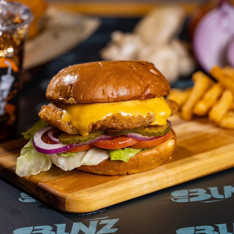 A picture of a fried chicken burger with delicious melted cheddar cheese. Yum!
