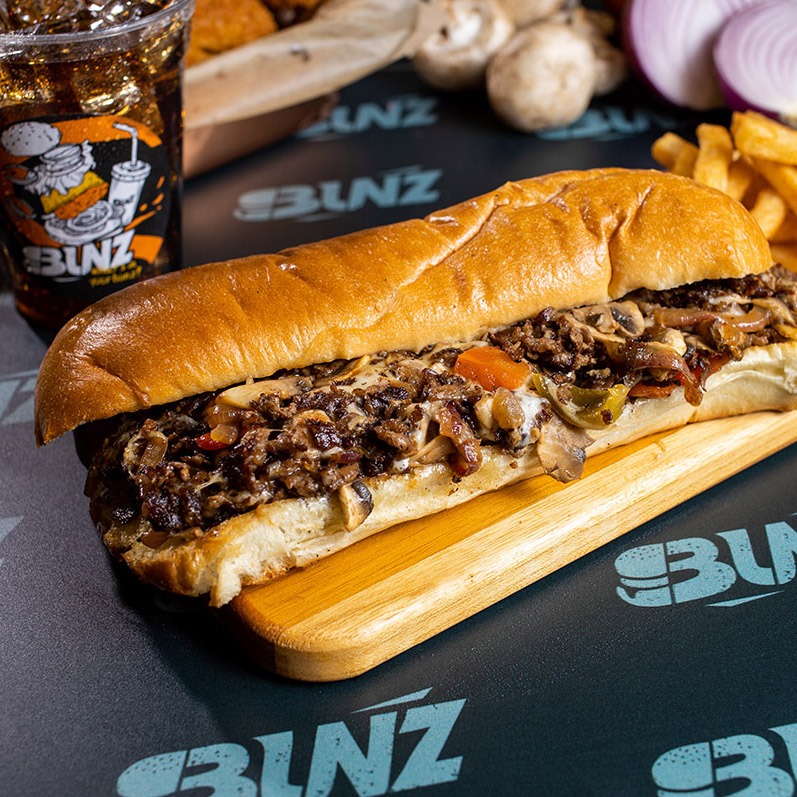 A picture of a delicious mushroom steak philly served inside of a toasted 12 inch roll.