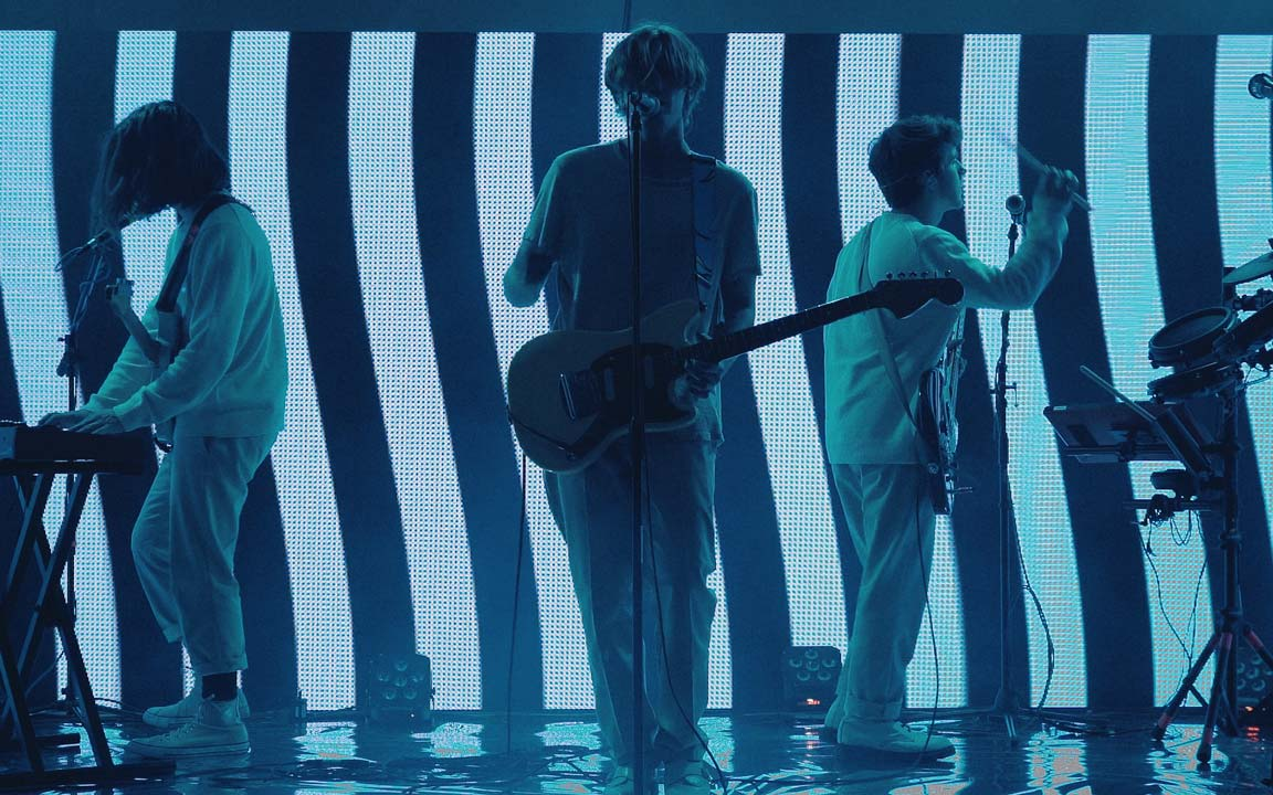 "A wide shot of the band in front of the LED wall stage we designed for the ""What Day Is It?"" live performance film."