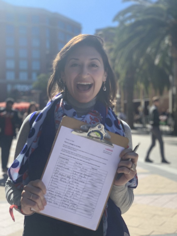 An excited Elena holding a clipboard with signatures of people pledging to take care of their trash