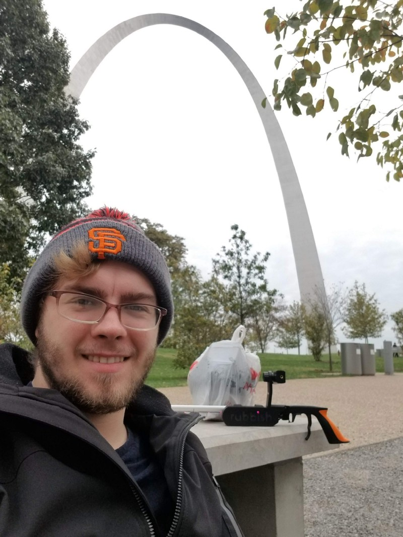 Adam with a bag of trash and his smart trash picker upper in front of the Gateway Arch in Saint Louis