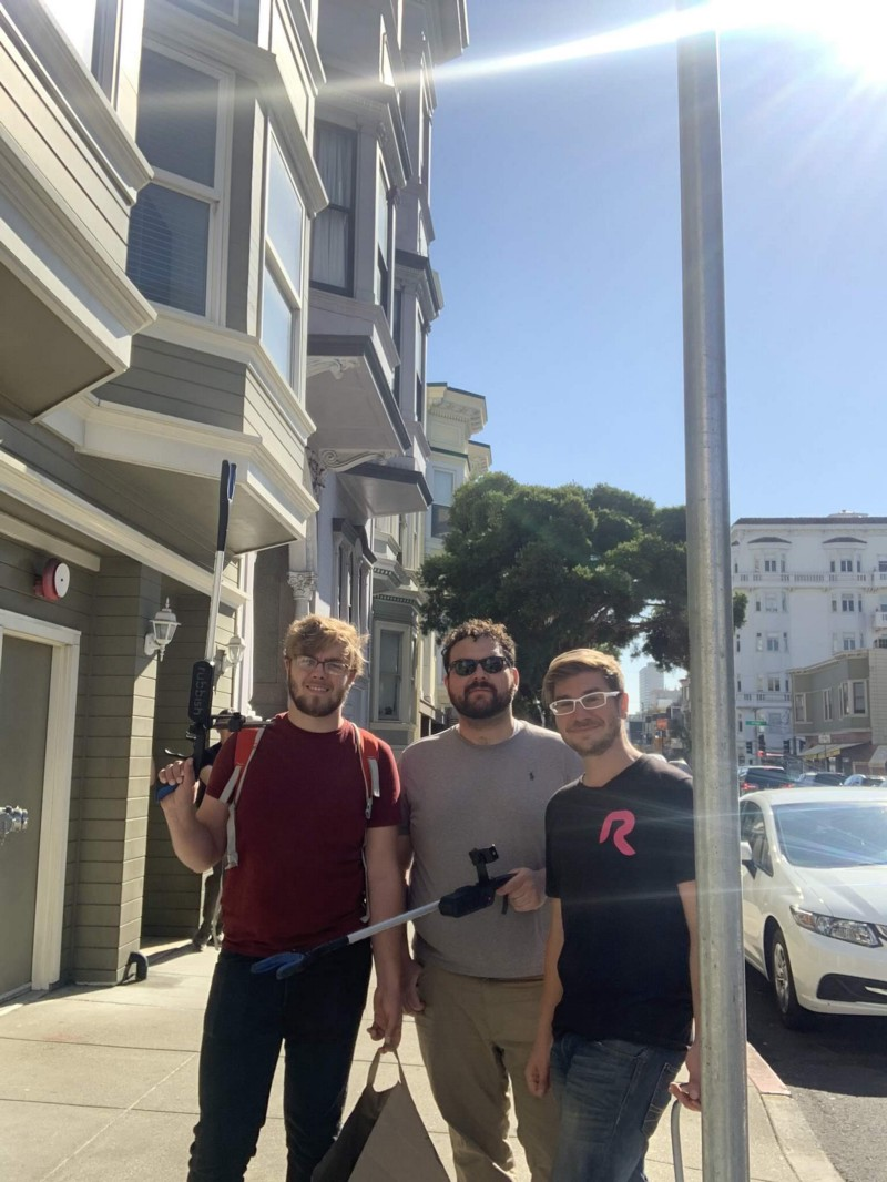 Adam, Felipe, and Emin taking a photo together with their smart trash picker uppers on the street of San Francisco
