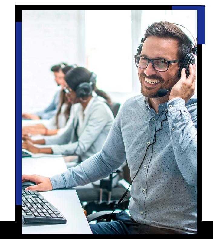 A imagem apresenta um homem de óculos sorrindo, utilizando um headphone e realizando atendimento (Call Center). Ao seu redor há mais pessoas fazendo a mesma atividade.