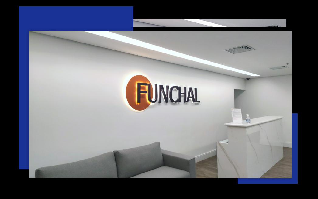 A imagem apresenta a recepção da Funchal Negócios com um sofá, uma mesa e o logo da empresa instalado na parede.