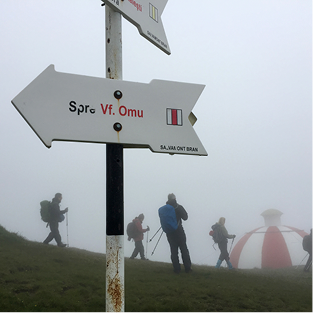 Sign in Romanian set against a backdrop of hikers dressed in cold weather gear around a red and white striped, domed tent.