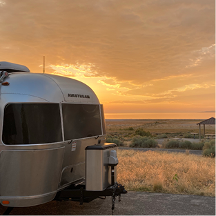 Showing the back end of a silver airstream against an orange sunset sky