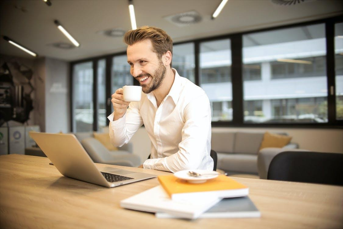 Depth of Field Photo of Man Sitting on Chair While Holding Cup in Front of Table
