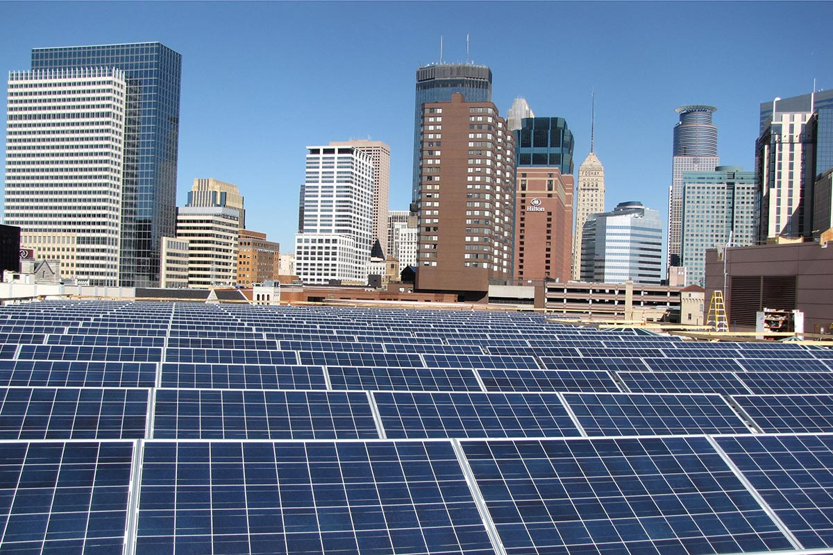 Solar panels on a roof with skyscrapers in the background.